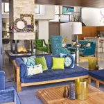 adorale futuristic eclectic interior style with blue sofa design and yellow cushions and wooden coffee table and natural view