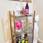 amazing bar cart accessories in metal cart with three shelves and scluptures and wine glasses plus liquors and limes