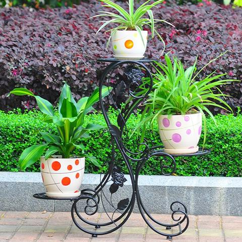 amazing black wrought iron stand idea with branch and polka dot potted plants