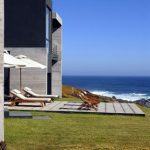 amazing view of beach modern house design with concrete outdoor living space in grassy meadow and boxy building