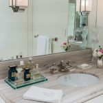 amazing white vanity dresser try made of glass on wooden top with single round sink beneath wall mirror with wall lamps