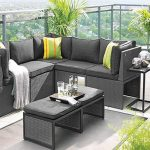 apartment balcony furniture in grey with sectional outdoor sofa and yellow cushions plus grey coffee table and end table plus grey rug and plants