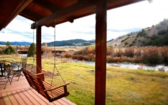 awesome garden porch swing set made of wooden material above wooden floor facing large grassy meadow with mountain view