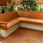 awesome outdoor corner bench decorated on the top of concrete wall and solid wooden floor and beautiful small garden behind the bench