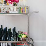 bar cart accessories with flower plus cute wine glass and straws and metal fruit bowl arranged on metal cart with wheels