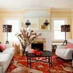 best red and white interior design with white sofa and patterned red area rug and black coffee table and fireplace and custom shade lamp