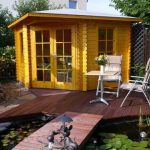 best small yellow compact home design with wooden outdoor patio deck and white chairs and rectangle table and glass window and wooden fence and garden