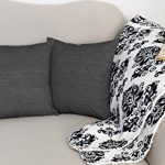 black-denim-square-throw-pillows-set-of-two-on-the-grey-sofa-and-glasses-and-books