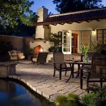 calming outdoor patio design with stone flooring and some cluster of seating with fireplace and coach lighting and pool