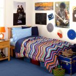 cheerful college dorm room idea wth chevron sheet and blue bedding and wooden nightstand and wall pictures and teasure box and blue flooring