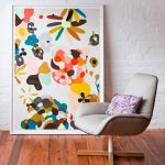 cheerful painting design for interior beneath white wall and creamy chair with cushion and wooden floor
