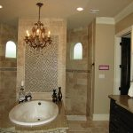 classic and luxurious bathroom design with modern shower and great black vanity with gold river granite and unique white sink and chandelier