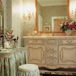 classic bathroom design with peach cabietry with carved details and black floral area rug and sleeve slip cover and framed wall mirror
