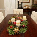 classic christmas dining table centerpiece idea with christmas balls and greenery and giant candle and acrylic holder