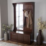 classic wooden coat rack idea with mirror and antique hooks and pottery decoration with indoor flower on wooden floor