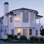 classical white two storey house design with open concept with tower and outdoor garden idea with modern lighting