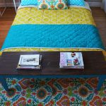 colorful moroccan diy floor rug design idea with floral pattern in blue yellow and green beenath bedding with blue and yellow sheet with black wooden bench