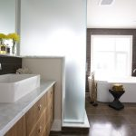 comfortable and tidy posh bathroom design idea with white freestanding bathtub and wooden vanity with white top and white siding and wooden flooring