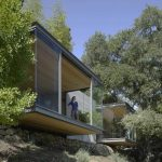 cool half hovering valley sillicon house design with open plan on rocky hill with shady trees surrounding