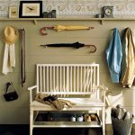 Country Foyer And Entryway Organization Ideas With White Bench And A Metal Fray Under The Bench And Floating Shelf Above The Bench For Decorative Items And Clock