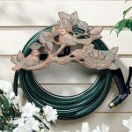 decorative-chickadee-garden-hose-holder-with-stylish-design-and-rust-free-aluminum-also-all-weather-paint-finishing-and-mounted-on-the-white-wooden-wall