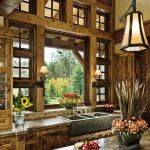 double height rustic kitchen design with wooden cbainetry and pendant and island with white marble op and glass window