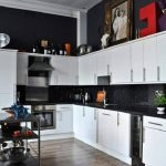 double white appliance in a black and white kitchen decor with wooden floor and portable kitchen cart and black siding
