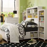 elegant and girly black and white college dorm room idea with storage headboard and black polka dot area rug and floral bedding sheet and glass window and green paint wall
