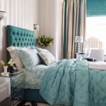 elegant bedroom idea with turquoise bedding sheet and tufted headboard and luxurious curtain and wallpaper and mirrored side table and creamy area rug