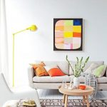 elegant white interior design with white sofa and colorful cushions and patterned area rug and wall picture and yellow floor lamp