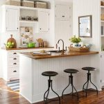 elegant white kitchen design with white cabinetry and wooden top and breakfast bar with black stools and blue runner rug