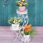 elegant white wrought iron stand for flower design idea with curving mode and colorful flowers on colorful pots