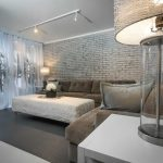 exclusive inteiror living room idea with white brick wall accent and white coffee table with gray sofa and white end table with unqiue table lamp