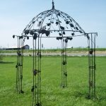 fascinating wrought iron pergola in black with pretty ornaments and green grasses aside the road