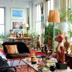 gorgeous bohemian eclectic style of interior with greenery and red accents and black chair and ststue and table lamp