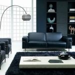 gorgeous exclusive black living room design with leather sofa and curved floor lamp and black storage and white coffee table and glass window
