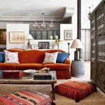 gorgeous interior design idea with orange couch and playful moroccan floor cushion and creamy area rug and light vintage coffee table and wooden room divider