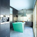gorgeous kitchen studio design with glass door idea and gray cabninetry and turquoise island with wall storage and concrete flooring