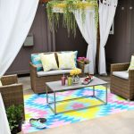 gorgeous rainbow diy floor rug design in yellow blue and pink colors with simple vintage coffee table and rattan sofa beneath wooden pergola