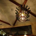 gorgeous refined wine bottle chandelier idea installed on the ceiling beneath exposed wooden beams with iron frame