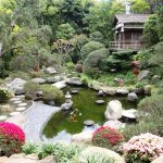 gorgeous small japanese garden design with pond and boulders and colorful flowers and small home cottage and concrete walkway