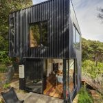 gorgeous tall black vinyl sided small compact house design with open plan and concrete outdoor patio deck with black chair