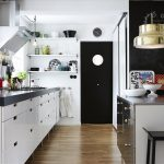 gorgeous white kitchen design idea with white wooden cabinetry and black siding accent and golden cool light bulb design idea