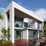 gorgeous white  two storey house design with contemporary style with glass facade and wooden outdoor patio deck