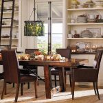 great christmas centerpiece on wooden classic dining table with brown leather chairs and super large wall shelves and wine bottle chandelier and rustic wooden ladder