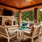 great outdoor patio dsign with wooden flooring and wooden chair with upholster and fireplace with stone mantel and pool and pergola