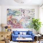 great scandinavian interior design with abstract painting on white wall with blue sofa and zebra patterned area rug and indoor plant and white pendant