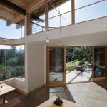 great sustainable home interior design with skylght and open plan and wooden furniture and siding and forest view