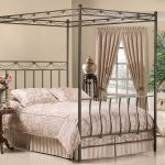 iron canopy bed frame of modern bedroom with stunning bedding plus round wooden night table beautified with flower vase and small comfy chairs plus pretty drape on windows