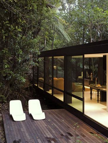 livable forest houe design with extended outdoor space with chaise lounge and open plan interior with black roof